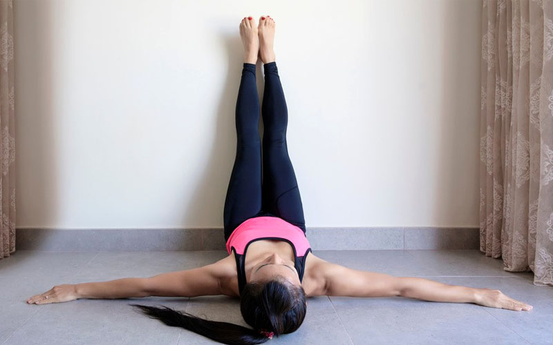 a woman doing legs up the wall pose