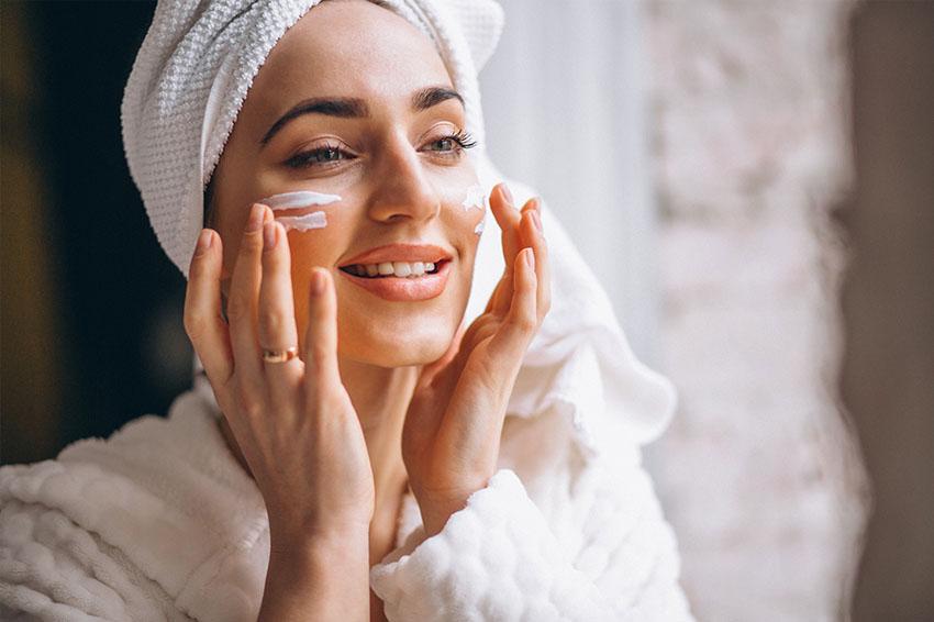 women applying retinol on face
